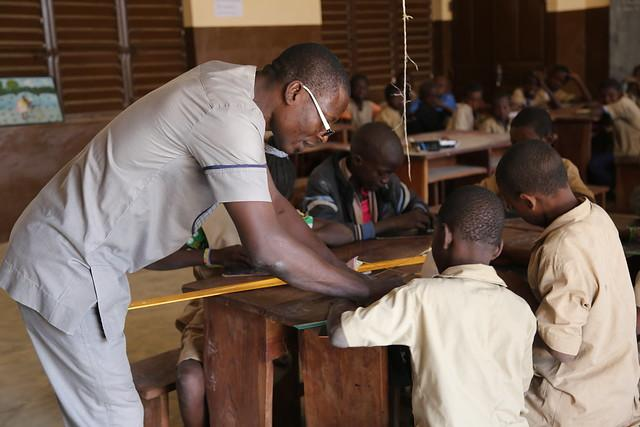 Teacher Léandre Benon and his students in class at The Akoitchaou primary school, located near Kandi, in the north of Benin. December 2018.